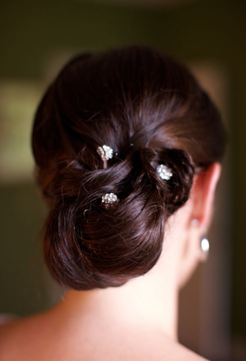 A bridal hairstyle with various accessories, including a feathered flower